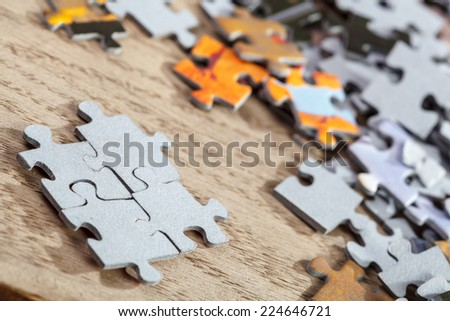 Closeup of  four connected jigsaw puzzle pieces on a table. Shallow depth of field - stock photo