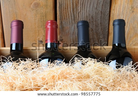 Closeup of four different wine bottles in a wooden crate with straw packing material. - stock photo