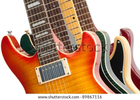 Closeup of four electric guitars on white. - stock photo