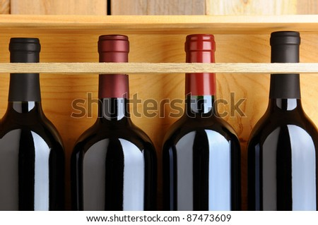 Closeup of four red wine bottles in a wooden case. - stock photo