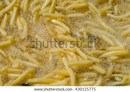 Closeup of french fries in hot boiling oil in the process of cooking  - stock photo