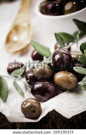 Closeup of fresh black olives and leaves in the kitchen for use as a cooking or salad ingredient - stock photo
