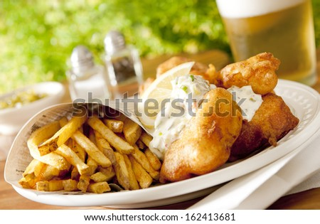 Closeup of fresh fish and chips and beer. - stock photo
