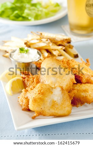 Closeup of fresh fish and chips with tartar sauce. - stock photo
