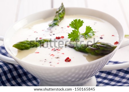 Closeup of fresh green asparagus tips in a bowl of cream of asparagus soup garnished with coriander - stock photo