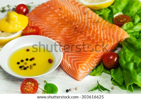 Closeup of fresh raw salmon fillet on wooden rustic table with shallow septh of field. Healthy food, diet or cooking concept. - stock photo