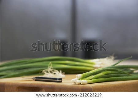 Closeup of fresh spring onions and knife on chopping board - stock photo
