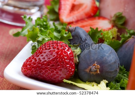 Closeup of fresh strawberries and figs on holiday table.