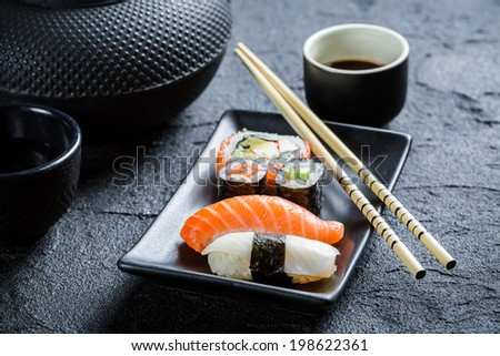 Closeup of fresh sushi served in a black ceramic - stock photo