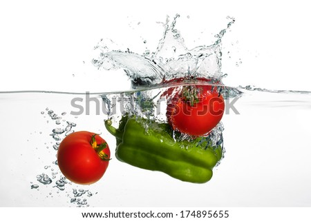 Closeup of fresh tomatoes and green Pepper falling into clear water with big splash isolated on white background. Healthy eating - stock photo