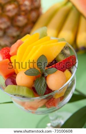 Closeup of fresh tropical fruit salad in cocktail glass. Kiwi, melon, papaya, mango, red grapes, strawberry and chocolate mint. - stock photo