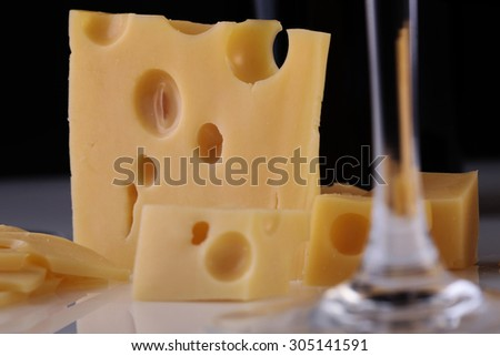 Closeup of fresh yellow delicious delicatessen dairy product of cheese slices near stem of crystal glass wine goblet standing on white table top on black background, horizontal picture - stock photo