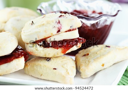 Closeup of freshly baked strawberry scones with butter and strawberry preserves. Selective focus with shallow depth of field. - stock photo