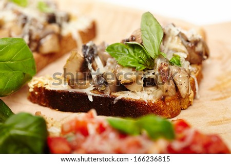 Closeup of freshly cooked mushroom bruschettas decorated with leaves of basil on a wooden board, selective focus - stock photo