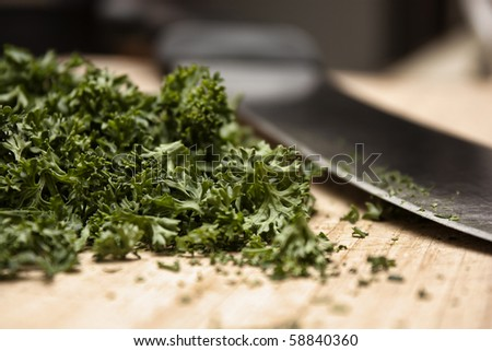 Closeup of freshly cut parsley next to a knife on a wooden cutting board. - stock photo
