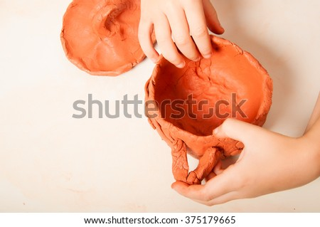Closeup of freshly made clay pot and child's hands