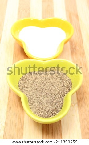 Closeup of freshly powdery pepper and salt in colorful bowl lying on wooden cutting board - stock photo