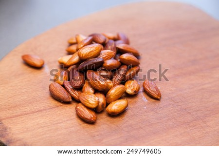 Closeup of freshly roasted almonds with selective focus - stock photo