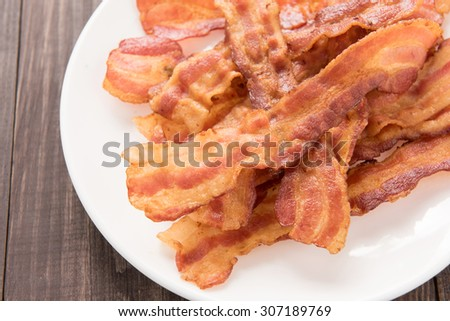 Closeup of fried bacon strips on white plate. - stock photo