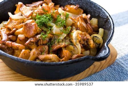Closeup of fried golden chanterelles in the cast-iron pan - stock photo