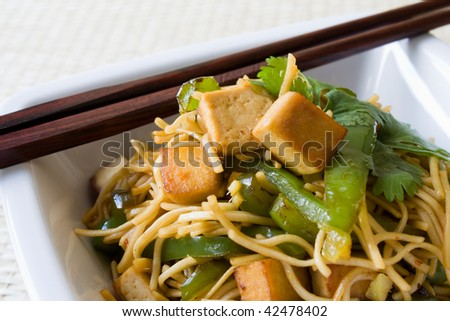 Closeup of fried noodles with tofu, coriander and green pepper.