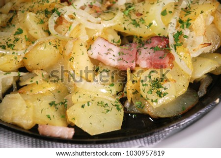 Closeup of fried potatoes with bacon and onion