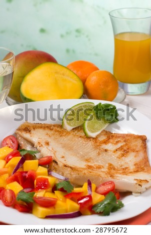 Closeup of fried skate (ray) with mango, cherry tomato and red onion salsa. Fresh fruits and glass of juice.