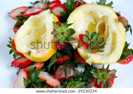 closeup of fruits (lemons and strawberries) scraps on a table. - stock photo