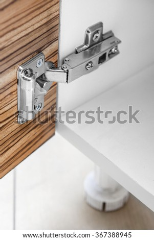 Closeup of furniture cabinet modern clip hinge with amortization - kitchen slow motion hardware - stock photo