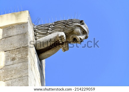 Closeup of gargoyle of St Francis of Assisi Church on the blue sky background, in Port Grimaud in the Var department in France - stock photo