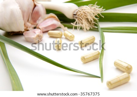 Closeup of garlic extract pills and fresh garlic leaves and cloves best suited for health, anti-cholesterol and alternative medicine ads - stock photo