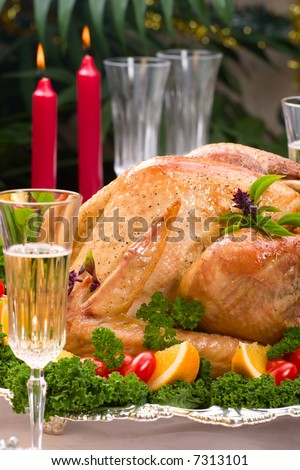 Closeup of garnished roasted turkey on Christmas decorated table with candles and flutes of champagne. Shallow dof. - stock photo