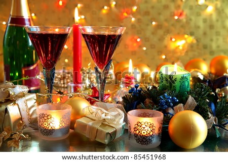Closeup of gifts,candle,baubles and glasses with red wine on golden background with lights. - stock photo