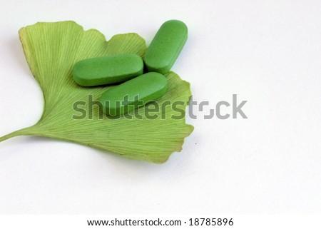 Closeup of Ginkgo Biloba and herbal pills - stock photo