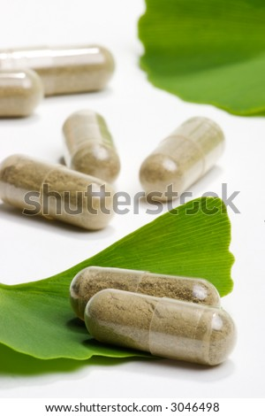 Closeup of Ginkgo Biloba extract pills and fresh Ginkgo Biloba leaves best suited for aged people alternative medicine ads - stock photo