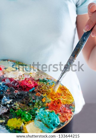 Closeup of girl holding brushes and palette - stock photo