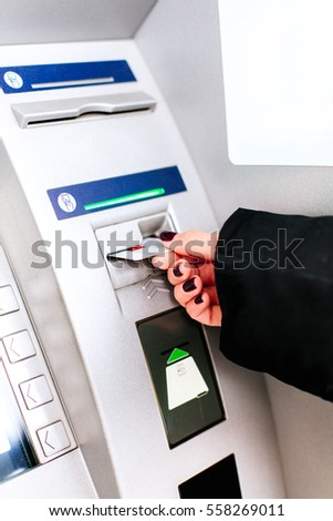 Closeup of girl holding shopping bags withdrawing money from ATM machine