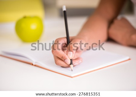 Closeup of girl sitting at the table and holding a pencil in hand. - stock photo