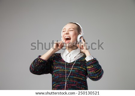 Closeup of Girl With Headphones Singing with her mouth wide open  On grey Background - stock photo