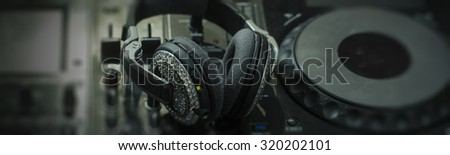 Closeup of glamour headphones with pastes and dj musical mixer professional console black color with many buttons and knobs in night club or studio on digital background, horizontal picture