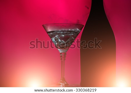 Closeup of glamour open full champagne wive sweet or dry drink green glass bottle and goblet with white smoke and ice for celebration christmas or new year on pink background, horizontal picture - stock photo