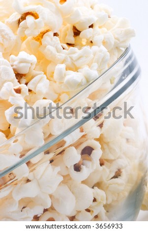 Closeup of glass bowl of popcorn - stock photo