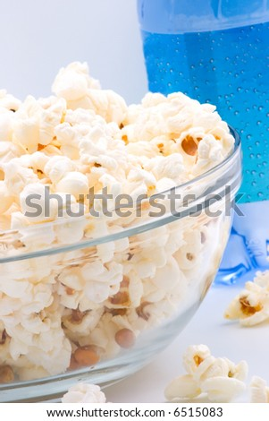 Closeup of glass bowl of popcorn and bottle of sparkling water in background - stock photo