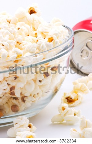 Closeup of glass bowl of popcorn and can of drink in background - stock photo