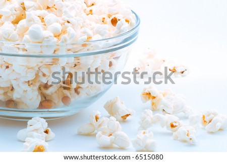 Closeup of glass bowl of popcorn with few peaces throw around - stock photo