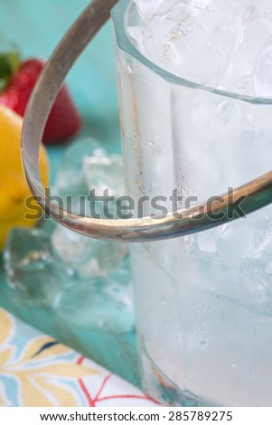 Closeup of glass bucket with ice cubes.