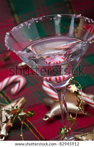 Closeup of glass of Candy Cane Martini and Christmas ornaments - stock photo