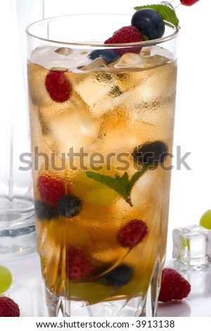 Closeup of glass of Kew Punch cocktail - vodka, sweet vermouth, gin, cherry brandy, orange curacao and assorted summer fruits with ginger ale and sparkling lemonade - stock photo