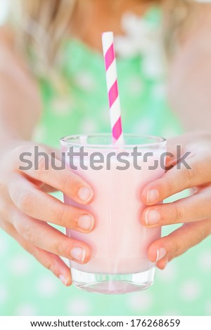 Closeup of glass of smoothie drink with straw held in hands by young girl - stock photo