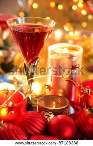 Closeup of glass with red wine and baubles,candle lights on gold background with twinkle lights. - stock photo